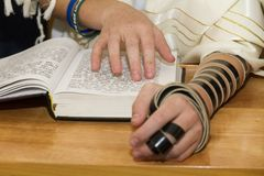 指向在圣经书sefer torah的一个词组的一个年轻人,当读祈祷在犹太仪式时 免版税库存图片