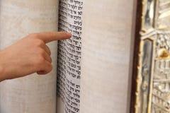指向在圣经书的一个词组的一个年轻人 库存图片