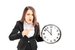 指向在壁钟的恼怒的年轻女实业家 免版税库存照片
