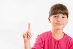 指向在复制空间的逗人喜爱的小女孩 库存照片