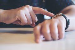 指向在她的工作时间的一块黑手表的女商人 免版税库存照片
