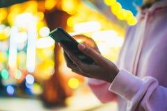 指向在屏幕智能手机的女孩手指在背景在夜大气城市照明的bokeh光在晚上街道defoc 免版税库存照片