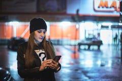 指向在屏幕智能手机的女孩手指在背景照明bokeh颜色光在夜大气城市 免版税库存图片