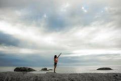指向在岩石的天空的妇女在Bakovern海滩,开普敦的日落 免版税库存照片