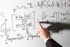 指向在平等算术标志的老师手指在whiteboard 数学和科学 免版税图库摄影