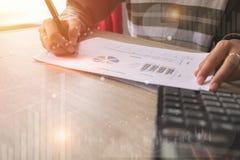 指向在数据纸数据的商人在与膝上型计算机的办公室桌上工作 概念事务和财务 库存照片