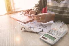 指向在数据纸数据的商人在与膝上型计算机的办公室桌上工作 概念事务和财务 图库摄影