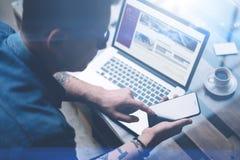 指向在智能手机屏幕上的商人手指 成人刺字了运转在膝上型计算机的晴朗的办公室的镜片的工友 免版税库存图片