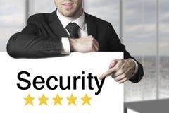 指向在标志安全的商人 库存照片