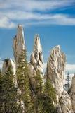 指向在森林上的天空的石石峰 库存照片
