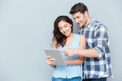 指向在灰色背景的个人计算机片剂的年轻夫妇 免版税库存图片