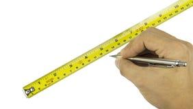 指向在白色背景的一卷测量的磁带的手特写镜头 库存图片