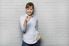 指向在砖墙,厕所前面的微笑的逗人喜爱的妇女一个手指 图库摄影