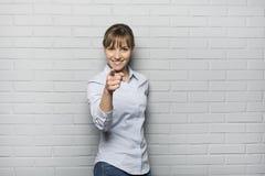 指向在砖墙,厕所前面的微笑的逗人喜爱的妇女一个手指 库存照片