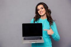 指向在空白的便携式计算机屏幕上的妇女手指 图库摄影