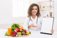 指向在空白的剪贴板的妇女营养师在办公室 库存图片