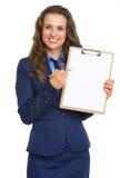 指向在空白的剪贴板的微笑的女商人 免版税库存照片