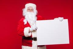 指向在空白的广告横幅的圣诞老人隔绝在与拷贝空间的红色背景 库存图片