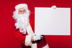指向在空白的广告横幅的圣诞老人隔绝在与拷贝空间的红色背景 库存照片