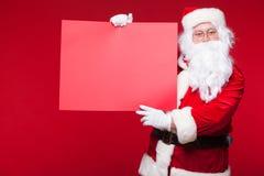 指向在空白的广告横幅的圣诞老人隔绝在与拷贝空间红色叶子的红色背景 库存照片
