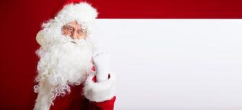 指向在空白的广告横幅的圣诞老人隔绝在r 免版税图库摄影