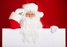 指向在空白的广告横幅的圣诞老人隔绝在r 免版税库存图片