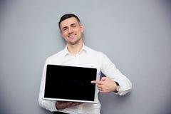 指向在空白的膝上型计算机屏幕上的微笑的商人手指 图库摄影