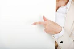 指向在空的横幅的女商人 免版税库存照片