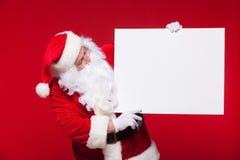 指向在红色背景的空白的广告横幅的圣诞老人与拷贝空间 库存图片