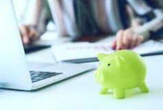 指向在综合报告图的妇女的手和计算在办公室特写镜头的财务 计算器,绿色存钱罐 免版税库存照片