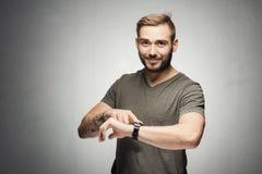 指向在腕子的一块手表的英俊的人 免版税库存照片