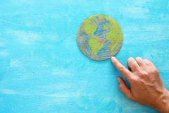 指向在蓝色木背景的地球地球的人手的顶视图图象 库存图片