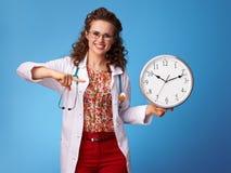 指向在蓝色的时钟的愉快的儿科医生医生 库存照片
