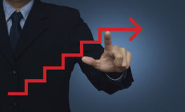 指向在蓝色backgroun的红色箭头台阶标志的商人 库存照片