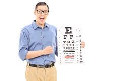 指向在视力检查表的激动的年轻人 免版税库存照片