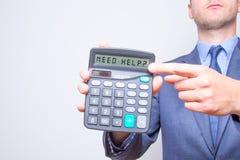 指向在计算器的年轻商人 需要帮助?标志 税务 免版税库存图片