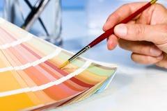 指向在调色板的颜色样品的艺术家手有油漆刷的 免版税库存照片