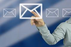 指向在迷离skys的一个信封标志的商人的手 免版税库存照片