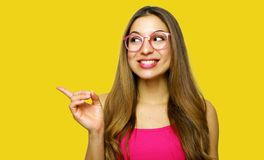 指向在黄色背景的女孩陈列看边 非常新和精力充沛美好年轻女人微笑愉快 免版税库存图片