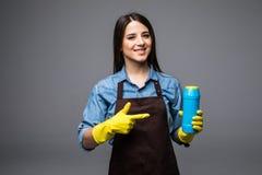 指向在更加干净的瓶的微笑的妇女主妇手指 查出在灰色 免版税库存图片