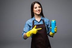 指向在更加干净的瓶的微笑的妇女主妇手指 查出在灰色 图库摄影