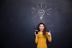 指向在黑板背景的智能手机黑屏上的愉快的妇女 库存图片