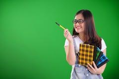 指向在绿色黑板的拷贝空间的滑稽的学校女孩 免版税库存照片