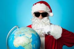 指向地球地图的圣诞老人 图库摄影