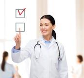 指向复选框的微笑的女性医生 库存照片