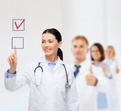 指向复选框的微笑的女性医生 免版税库存照片