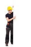 指向大白色横幅的建筑工人 库存图片