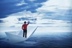 指向天空的亚裔商人,站立在纸小船 图库摄影