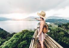 指向天际的愉快的妇女感觉任意旅行在激动人心的背景的世界 免版税库存图片
