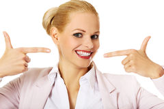 指向她愉快的微笑的女商人 免版税库存图片